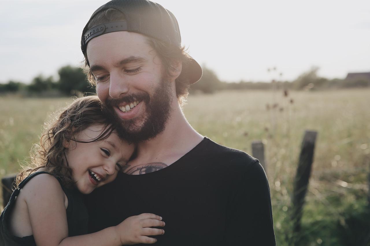 Glücklicher Mann mit Tochter, beide lächeln