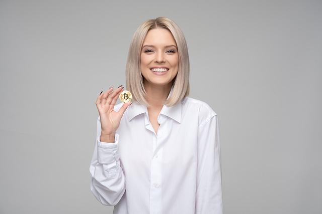 Elegant gekleidete Frau hält Bitcoin und lächelt